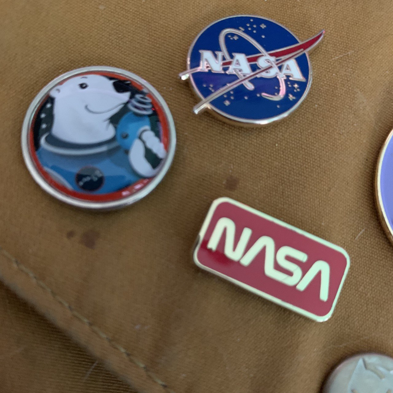The original and 1976 NASA logos, as enamel pins, next to a pin with the mascot of the 75th World Science Fiction Convention, 'Major Ursa'