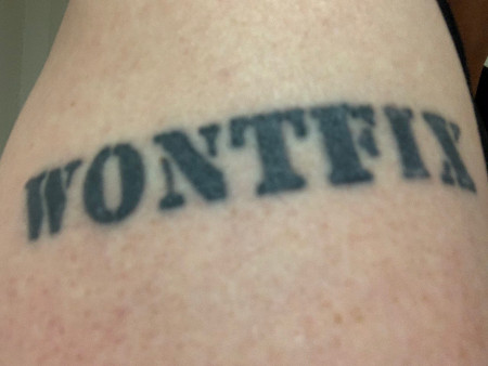 "A tattoo of the word ""WONTFIX"" in black stencil-style lettered ink on a white person's shoulder"